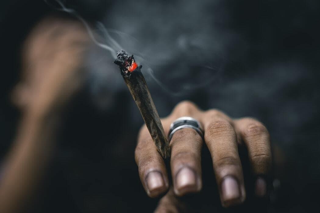 cannabis smoker holding alight joint